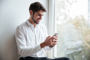 Cheerful businessman dressed in white shirt sitting in cafe and look at phone while chatting