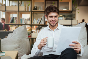 Cheerful businessman dressed in white shirt sitting in cafe and reading documents while drinking tea. Looking at documents.