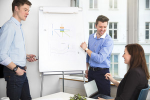 Cheerful Businessmen Looking At Female Colleague In Meeting
