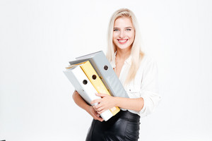 Cheerful businesswoman standing and holding folders over white background