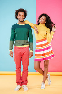 Cheerful carefree african young couple standing and flirting over colorful background
