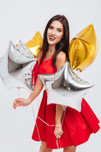 Cheerful charming young woman in red dress holding star shaped balloons and having fun over white background