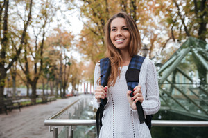 Cheerful charming young woman with backpack walking in park