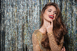 Cheerful charming young woman with long hair and bright makeup standing and laughing over sparkling background