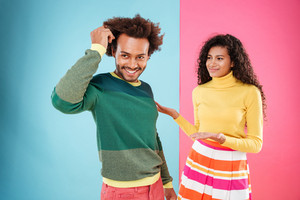 Cheerful confident african young man standing in front of his confused girlfriend over blue and pink background