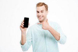 Cheerful confident young man showing blank screen mobile phone over white background