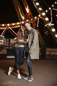 Cheerful couple in amusement park. in warm clothes. full length photo