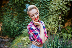 Cheerful cute pinup girl in plaid shirt standing and smiling in the garden