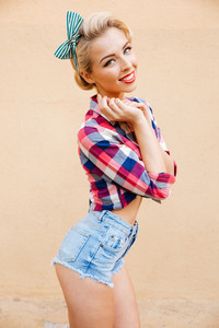Cheerful cute pinup girl in plaid shirt standing and smiling over pink background