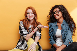 Cheerful cute redhead girl sitting and showing her african american friend over yellow background