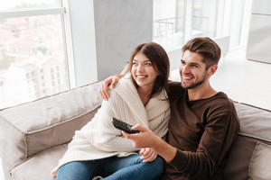 Cheerful cute young couple hugging and watching TV on couch at home