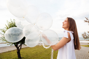 Cheerful cute young woman holding balloons and having fun on promenade