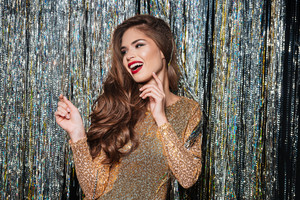 Cheerful cute young woman in evening dress laughing and having fun over shining background