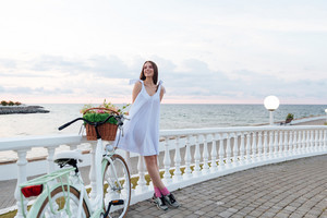 Cheerful cute young woman with bicycle standing on promenade