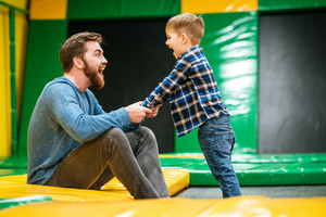 Cheerful dad and son having fun and playing together at indoor playground