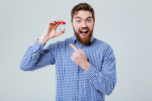 Cheerful excited bearded young man standing and pointing on bottle of pills over white background