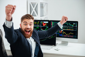 Cheerful excited young businessman with raised hands shouting and celebrating success at workplace in office