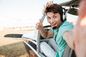 Cheerful excited young pilot sitting in cabin of small airplane and showing thumbs up