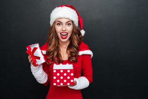 Cheerful excited young woman in santa claus costume opening gift box over black background