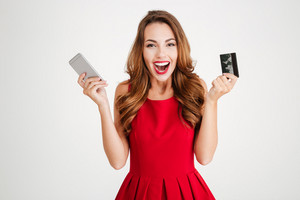 Cheerful excited young womna with mobile phone and credit card over white background
