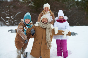 Cheerful family of four having fun in winter park