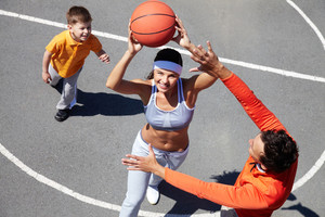 Cheerful family of three playing amateur basketball