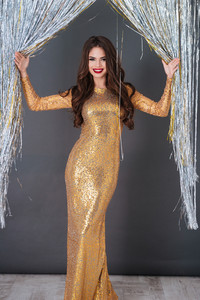 Cheerful gourgeous young woman in golden dress standing over sparkling decorations background