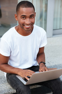 Cheerful handsome african american young man sitting and using laptop outdoors