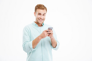 Cheerful handsome young businessman standing and using smartphone over white background