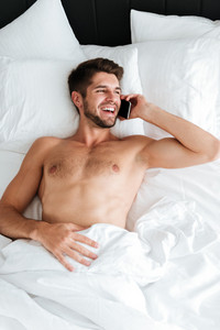 Cheerful handsome young man lying in bed and talking on mobile phone