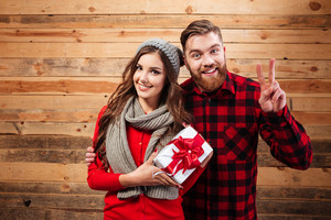 Cheerful happy couple in winter wear standing and holding gift box isolated on wooden background