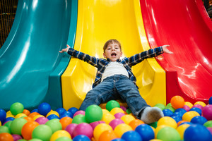 Cheerful joyful little boy playing on slide and pool with colorful balls