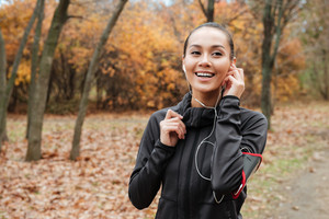 Cheerful lady runner in warm clothes and earphones in autumn park. Look aside.