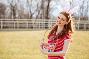 Cheerful laughing girl wearing bunny ears and holding easter basket with painted eggs outdoors
