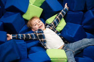 Cheerful little boy lying in pool with soft cube pillows at indoor playground