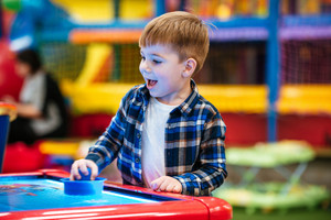 Cheerful little boy playing air hockey game and having fun at indoor playground