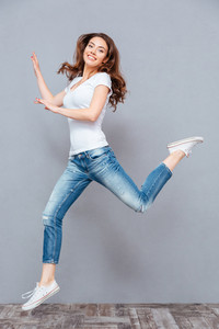 Cheerful lovely young woman jumping and having fun