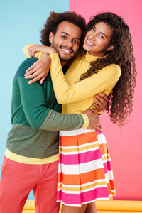 Cheerful loving african young couple standing and embracing
