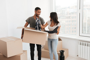 Cheerful loving couple standing near unpacked boxes. Look at each other. Man holding box with clothes.
