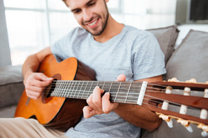 Cheerful man playing on the guitar while sitting on sofa at home. Focus on guitar.