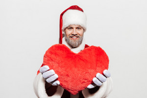 Cheerful man santa claus holding and showing red heart