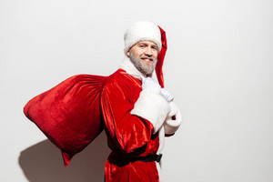 Cheerful man santa claus holding gift sack