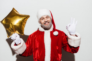 Cheerful man santa claus with golden star shaped balloon showing ok sign