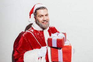 Cheerful man santa claus with present sack holding gift boxes