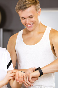 Cheerful man with a smart sport watch at fitness gym