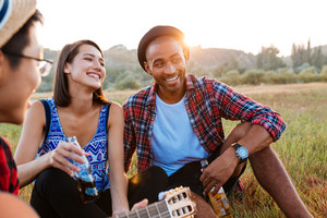 Cheerful multiethnic young couple drinking beer and soda with friends outdoors