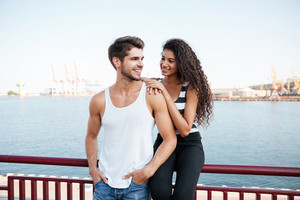 Cheerful multiethnic young couple in love standing in port
