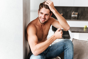 Cheerful muscular young man drinking coffee on the kitchen at home