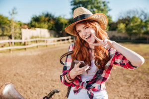 Cheerful playful young woman cowgirl in hat using cell phone and showing peace sign