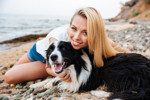 Cheerful pretty young blonde woman sitting and hugging her dog on the beach